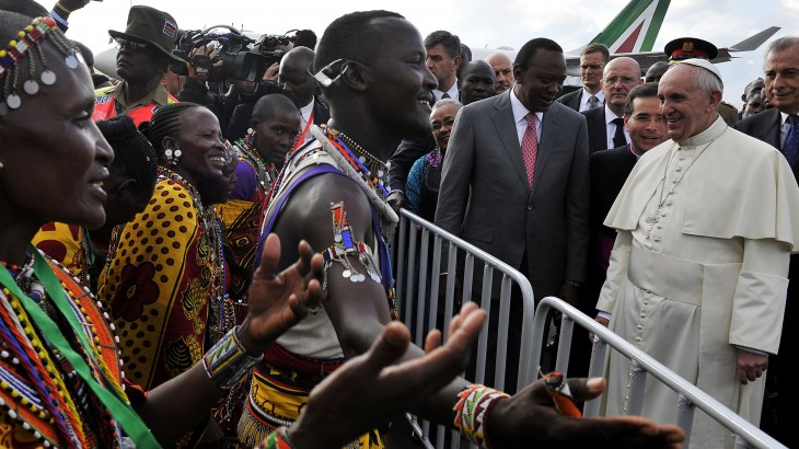 Pope Francis (Foreground-R) stands beside Kenya's President Uhuru Kenyatta as they watch traditional dancers after he arrived at the Jommo Kenyatta International airport in Nairobi on November 25, 2015.  Pope Francis landed in Kenya's capital Nairobi Wednesday on the first leg of a landmark trip to Africa, with huge crowds, choirs and dancers waiting to greet him. The flags of both Kenya and the Vatican flew from the airplane's cockpit as it taxied to a stop, where Francis was met by Kenyan President Uhuru Kenyatta with a red carpet welcome.  AFP PHOTO / SIMON MAINA / AFP / SIMON MAINA