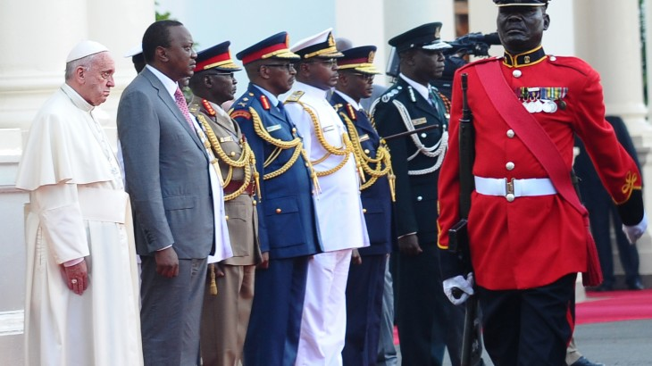 """Pope Francis (L) and Kenyan president Uhuru Kenyatta (2nd L) stand in line during a welcome ceremony for Pope's visit at the State House of Nairobi on November 25, 2015. Pope Francis said the world was facing a """"grave environmental crisis"""" as he arrived in Kenya on Wednesday on a landmark Africa trip just days before a crucial UN summit aimed at curbing climate change. He also warned of the need to tackle poverty as a key driver of conflict and violence as he kicked off a landmark Africa trip fraught with security concerns and urged Kenya's leaders to work with """"transparency"""" to ensure a fair distribution of national resources as criticism grows over runaway graft in this east African country. AFP PHOTO / GIUSEPPE CACACE / AFP / GIUSEPPE CACACE"""