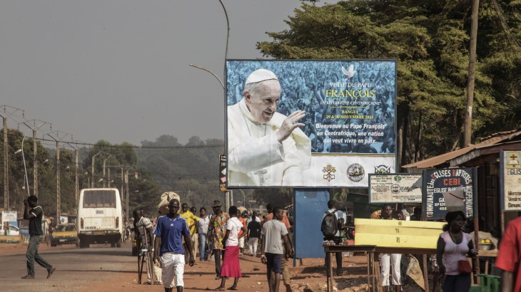 People walk by a billboard welcoming Pope Francis ahead of his visit in Bangui on November 25, 2015. Pope Francis on November 25 warned of the need to tackle poverty as a key driver of conflict and violence as he kicked off a landmark Africa trip fraught with security concerns. AFP PHOTO / GIANLUIGI GUERCIA / AFP / GIANLUIGI GUERCIA